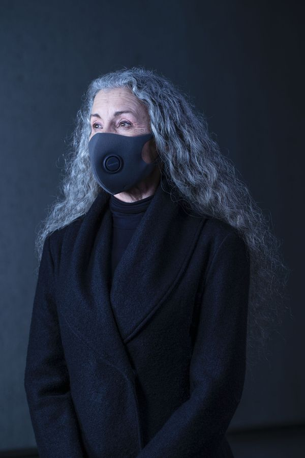 Photo of artist wearing black face mask with long greying hair