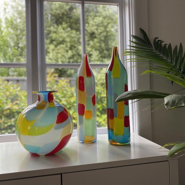 Three colourful glass vessels sitting on a windowsill.
