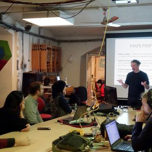 Josh Harle speaking to a group of people seated around a table in front of a slide presentation.