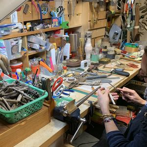 Female seated at a jewellers bench in a crowded and busy studio space, working with her hands on an object