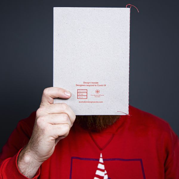 Man with red shirt holding a book in front of face