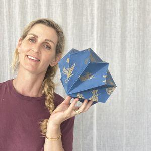 An artist holding an origami star shape