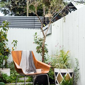Photo of  a small courtyard with chair draped with scarf and mug.