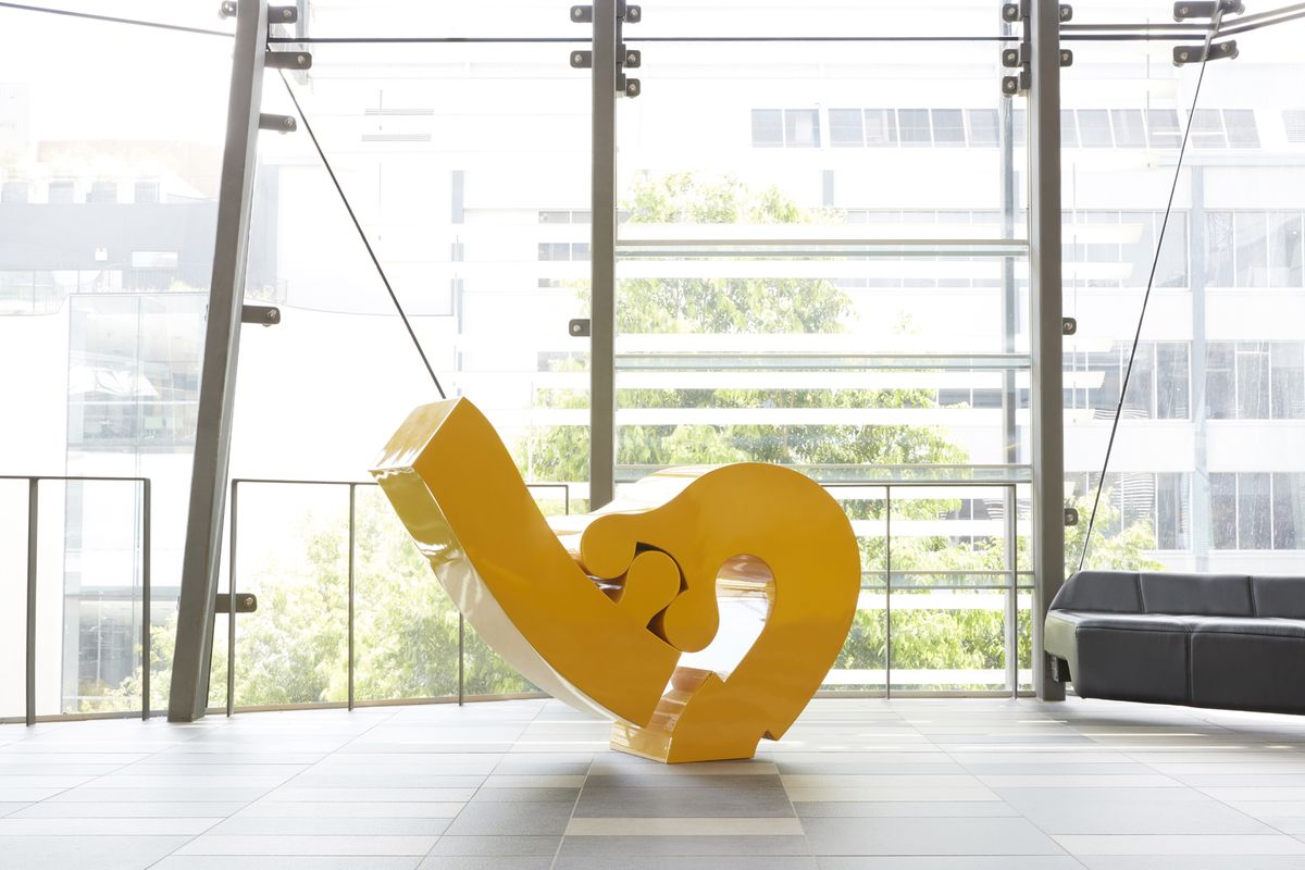 A photo of a yellow sculpture with to interlocking parts in front of a window