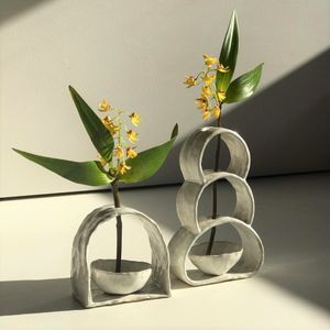 Two qhite ceramic arch shapes vases containing yellow flowers standing on a table.