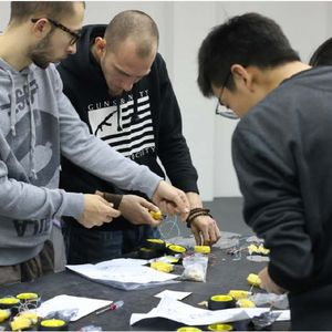 Group of people assembling robot components at a table during a workshop.