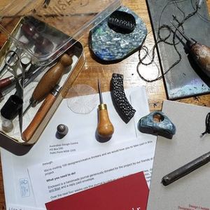 a group of books, papers and tools assembles for making something