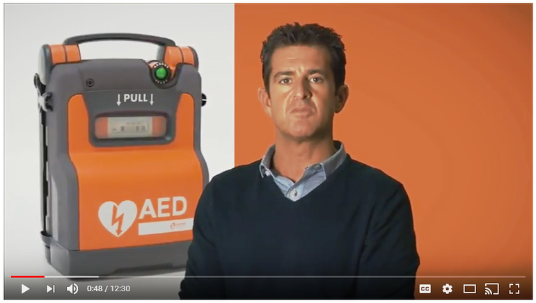 A still image from a YouTube video. The image features an orange AED and a man speaking. The background is orange.