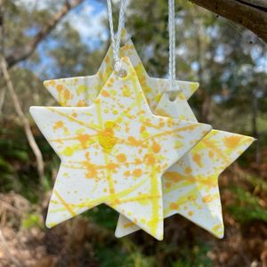 Close up of ceramic Christmas star decorations with yellow splashes hanging in a bush outside