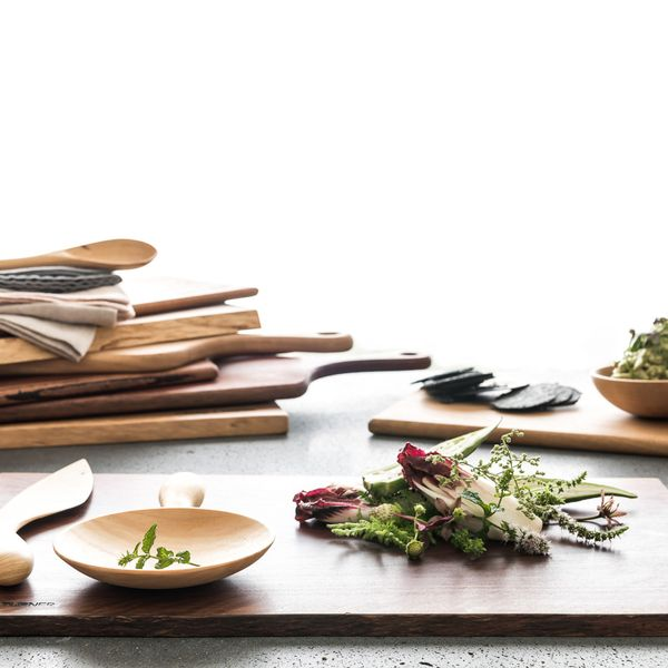 A stack of wooden chopping boards, plus some wooden utensils arranged on a table.
