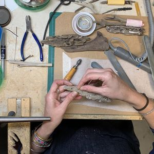 Hands holding a small piece of drift wood at a jewellers bench, the table is scattered with tools and pieces of driftwood