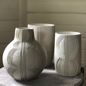 Three white ceramic vessels standing on a table against a white timber wall