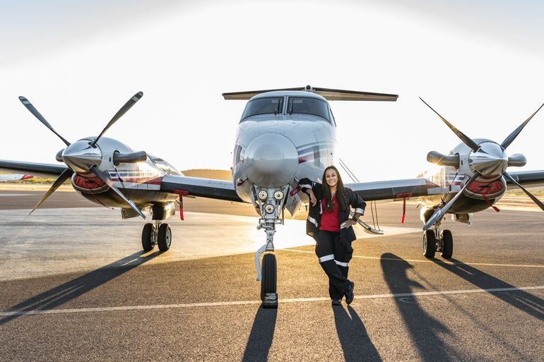 Staff stands next to plane