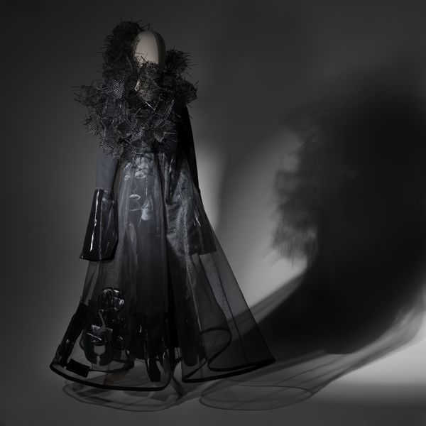 A mannequin wears a floor length, long sleeved black dress made from sheer fabric and shiny black pleather details