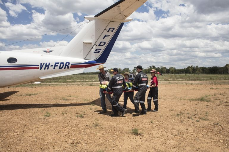 Flying Doctor Crew Carry a Patient to the Plane