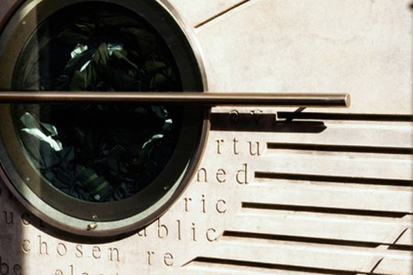 Photo of a concrete wall with horizontal indents in it and a circular window inset to the left of the image with clothing inside.