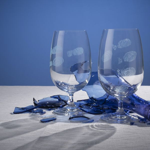 Two wine glasses with engraved fingerprints and a shattered blue glass bottle