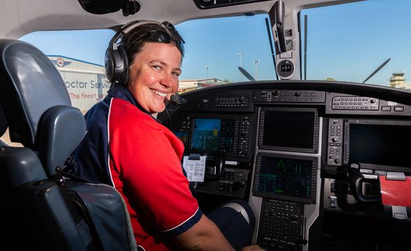 RFDS Pilot Heather Ford sits in the cockpit of a Pilatus PC12. She is wearing a headset and smiling.