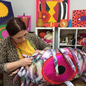 Female in vibrant studio space stitching a large soft sculpture in the shape of an eye