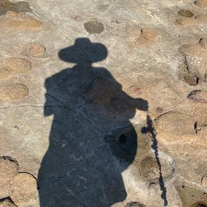 A shadow of the artist is cast onto a rock