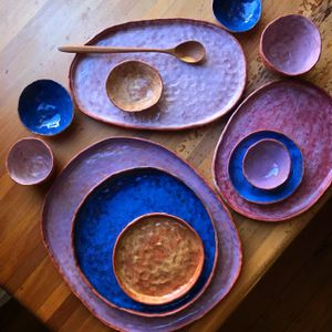 A selection of blue and purple ceramic plates and bowls arranged on a table