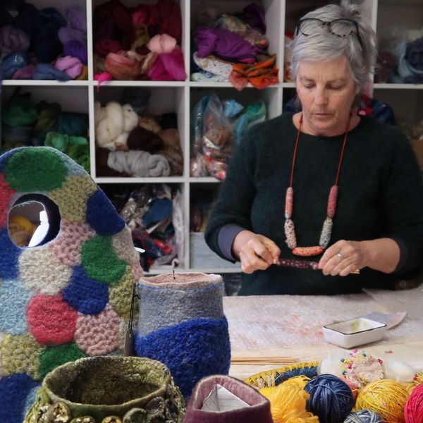 A portrait of fibre artist Gillian Brooks working in her studio at a table, with shelves full of felt in the background.