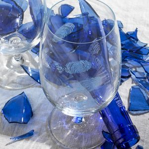 shattered blue glass bottle and clear glasses tumblers with engraved fingerprints on the surface