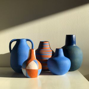 Five blue and orange ceramic vessels standing on a table against a white wall