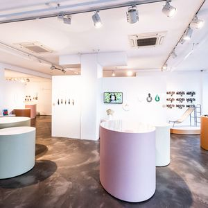 Photo of gallery featuring pink and beige round cabinets and a concrete floor.