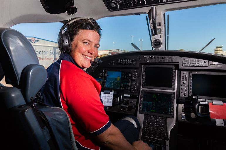 RFDS Pilot Heather Ford in the cockpit of a Pilatus PC12 aircraft. She is smiling and wearing a headset.