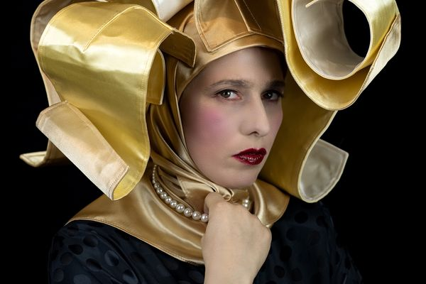 An image of a woman wearing an elaborate gold headers looking directly at the camera.