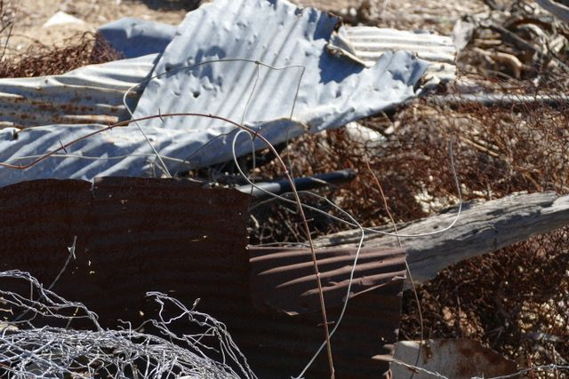 Photo of wire and corrugated iron in dry grass