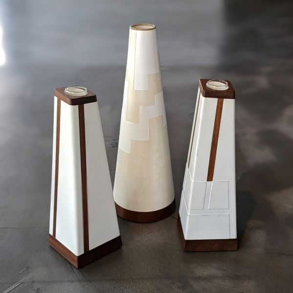Three tall pyramid shaped vases with white and wood finish standing on grey floor