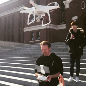 Josh Harle operating a drone on a flight of steps outside.