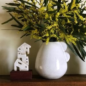 A large white ceramic vase and a small ceramic sculpture shaped like a stack of tiny houses, sitting on a table.