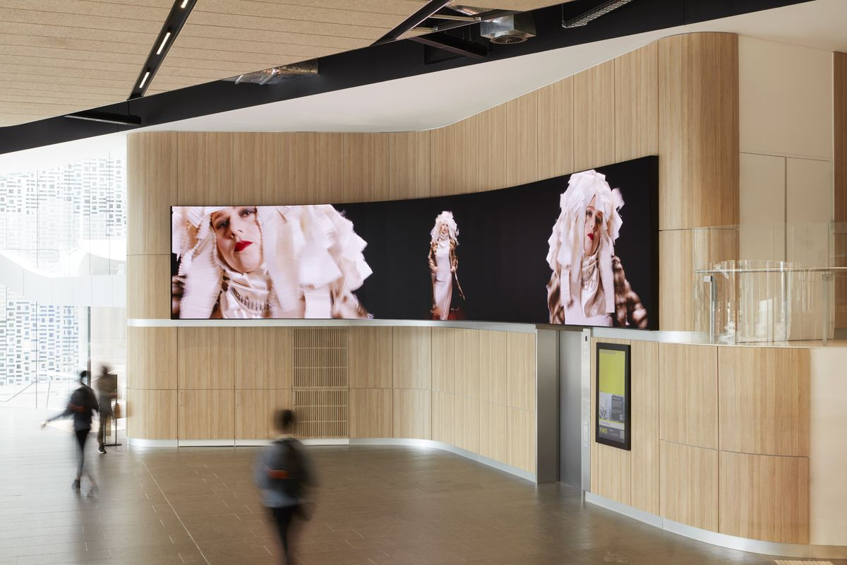 A photograph of a wide digital screen in a foyer with a woman in a headdress on the screen.