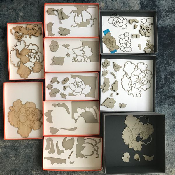 A series of laser cut flowers made of wood are in little boxes on the ground, a pair of feet is visible from above