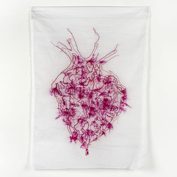 An embroidery of a red and pink anatomical heart, containing loose threads and fibres