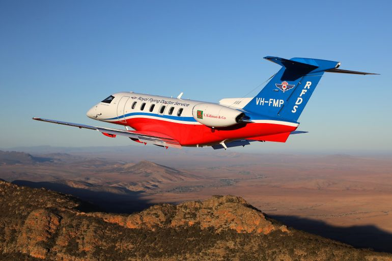 An aeromedical jet with RFDS branding flies above brown, rocky outback landscape.