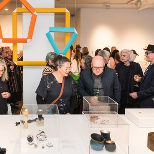 view inside a gallery open with people looking at tables and bright coloured paper decorations in the shape of jewels.