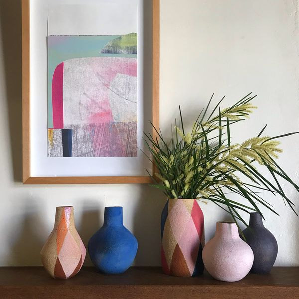 A group of brightly coloured ceramics vases sitting on a sideboard, below a bright coloured artwork.