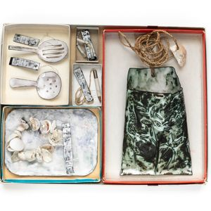 Cardboard tray with three compartments, various items made from pearl shell