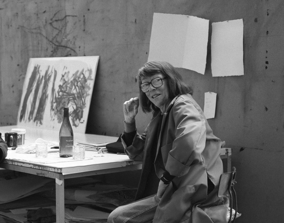 Black and white photo of artist Joan Mitchell sitting at table