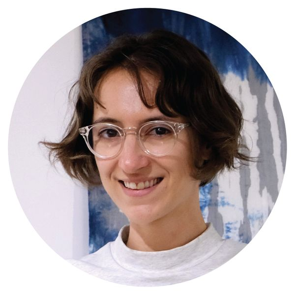 Photo of a woman with brown short hair wearing round glasses