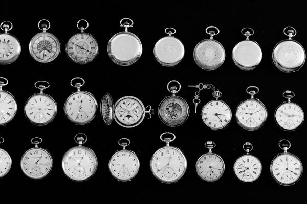 Various vintage pocket watches laid out on a table