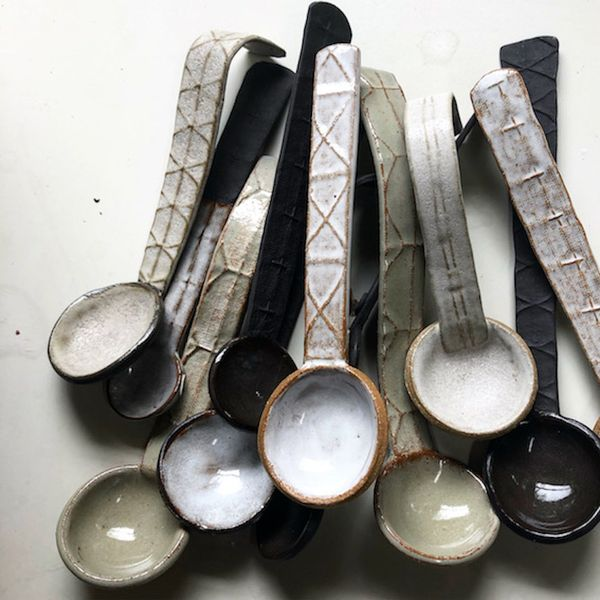 A collection of brown and cream textured ceramic spoons laid out on a flat surface.