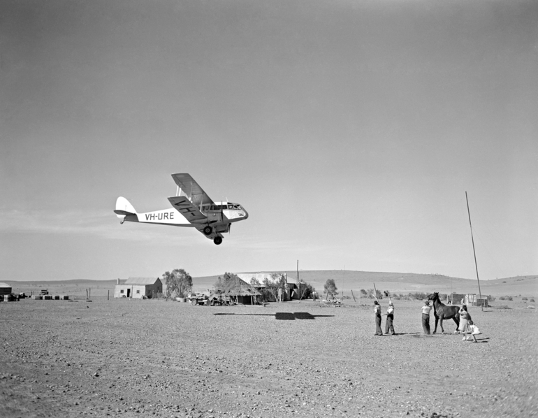 The Barlows look up at the Flying Doctor's De Havilland Dragon departs the Veldt station