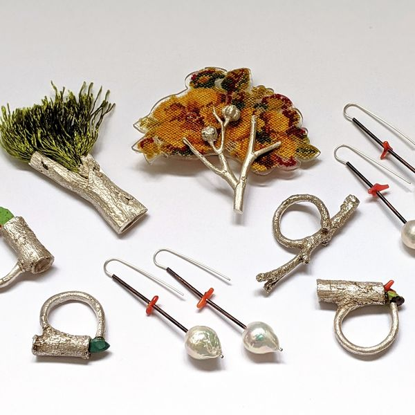 Collection of jewellery items including two silver tree brooches, four silver rings and two pairs of silver and freshwater pearl earrings.