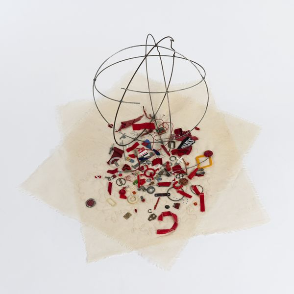 circular metal frame sitting on cream textile square cut off's with an assortment of red small found objects