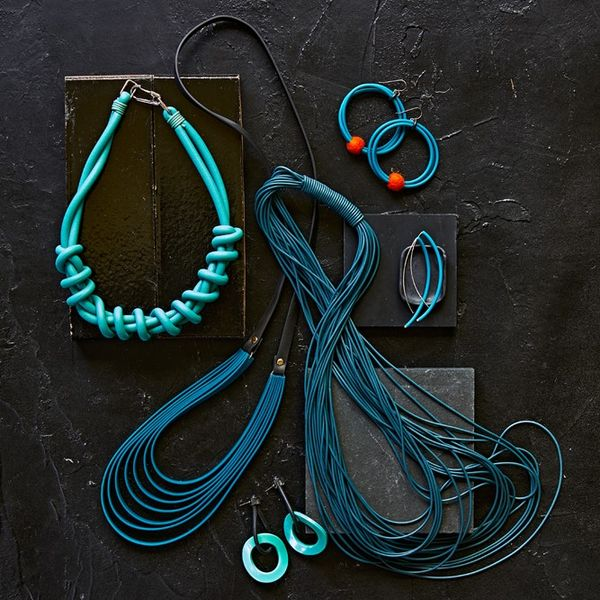 Collection of teal blue coloured Recycled Acrylic and Rubber earrings and necklaces against a dark background